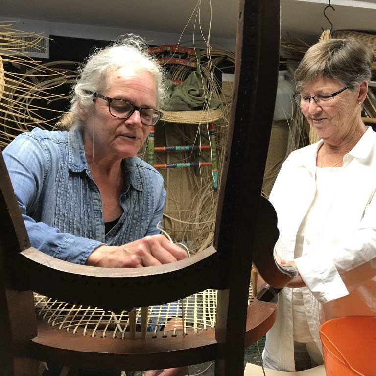 Pamela Foster teaching Margaret Good in Splint Seat Weaving
